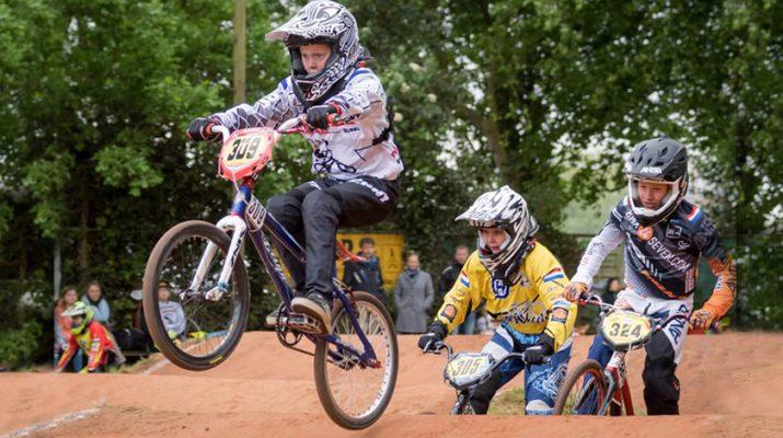 BMX'er rijdt op zijn achterwiel terwijl de concurrentie hem op de hielen zit